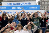 Students making the shelter sign at UNHCR tents and destroyed Darfur village set up on London Trafalgar Square to commemorate World Refugee Day. UK 2008 - Howard Davies - 18-06-2008