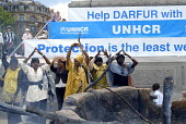 A Sudanese refugee women's group perform in front of a mock up destroyed Darfur village created by UNHCR in Trafalgar Square to commemorate World Refugee Day. UK 2008 - Howard Davies - 18-06-2008