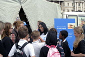 A volunteer speaks with pupils in refugee tents set up by UNHCR at Trafalgar Square to commemorate World Refugee Day. UK 2008 - Howard Davies - 2000s,2008,activist,activists,aid agency,assistance,camp,CAMPAIGN,campaigner,campaigners,CAMPAIGNING,CAMPAIGNS,camps,child,CHILDHOOD,children,day,DEMONSTRATING,demonstration,demonstrations,Diaspora,di