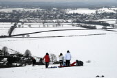 Families snowboarding after heavy snow on Clayton Hill, Sussex, UK - Howard Davies - 2000s,2009,child,CHILDHOOD,children,CLIMATE,conditions,country,countryside,downhill,heavy,hill,hills,holiday,holidays,juvenile,juveniles,kid,kids,Leisure,LFL,LFL Leisure,LIFE,outdoors,outside,people,p