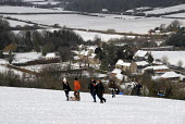 Families sledging after heavy snow on Clayton Hill, Sussex, UK - Howard Davies - 2000s,2009,adolescence,adolescent,adolescents,child,CHILDHOOD,children,CLIMATE,conditions,country,countryside,heavy,hill,hills,holiday,holidays,juvenile,juveniles,kid,kids,Leisure,LFL,LIFE,outdoors,ou
