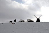 Families sledging after heavy snow on Clayton Hill, with a windmill, Sussex, UK - Howard Davies - 2000s,2009,CLIMATE,conditions,country,countryside,exercise,exercises,exercising,heavy,hill,hills,holiday,holidays,Leisure,LFL,LIFE,outdoors,outside,PEOPLE,precipitation,recreation,RECREATIONAL,rural,S