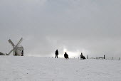 Families sledging after heavy snow on Clayton Hill, with a windmill, Sussex, UK - Howard Davies - 2000s,2009,CLIMATE,conditions,country,countryside,downhill,heavy,hill,hills,holiday,holidays,Leisure,LFL,LIFE,outdoors,outside,PEOPLE,precipitation,recreation,RECREATIONAL,rural,Severe Weather,sled,sl