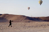 An Egyptian child watches tourists flying in hot air balloons near Luxor, Egypt 2008 - Howard Davies - 12-04-2008