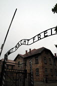 "Entrance with German for ""Work brings Freedom"" or ""work shall set you free"" or ""will free you"" above the gates at Auschwitz concentration camp, Poland - Howard Davies - 2000s,2008,ACE,against,anti,anti semitic,Anti Semitism,antisemitic,antisemitism,Auschwitz,BAME,BAMEs,bigotry,BME,bmes,camp,camps,chambers,communicating,communication,concentration,culture,dead,death,d"