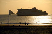 Holiday makers on the beach at Calais with cross channel ferry leaving port, France 2009 - Howard Davies - 14-07-2009