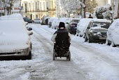 A disabled person using their wheelchair on an icy road during a winter freeze of 2009. Brighton - Howard Davies - 2000s,2009,access,age,ageing population,AUTO,AUTOMOBILE,AUTOMOBILES,AUTOMOTIVE,bound,car,cars,cities,city,disabilities,disability,disable,disabled,disablement,elderly,freeze,freezing,highway,ice,icy,i
