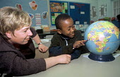 Refugee child at his new school with a teacher offering supplementary English classes. The boys family have recently arrived in the UK as part of Gateway a UK government resettlement programme. The re... - Howard Davies - 01-08-2004