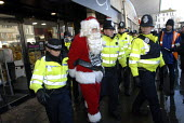 Santa Claus is arrested by police after gluing his hands to a shop front during a protest by National Day of Action against Tax Avoidance at Arcadia Group shops owned by Sir Philip Green who is an all... - Howard Davies - 18-12-2010