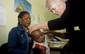 Family who are seeking asylum in Ireland visiting the Doctor at a Direct Provision Centre established by the Irish Government to house and care for refugees until their cases have been decided upon. C... - Howard Davies - 01-08-2004