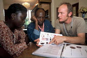Refugee families from Liberia at an orientation meeting with an aid worker from Migrant Helpline having just arrived in the UK as part of Gateway a UK government resettlement programme. The refugees h... - Howard Davies - 01-08-2004
