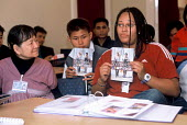 A support worker from Migrant Helpline briefs refugee families from Burma at a reception house having arrived in the UK as part of Gateway a UK government resettlement programme. The refugees had live... - Howard Davies - 2000s,2004,aid agency,aid workers,assistance,BAME,BAMEs,Black,BME,bmes,britain,burma,burmese,child,CHILDHOOD,children,Diaspora,displaced,diversity,ethnic,ethnicity,eu,europe,european,europeans,FEMALE,