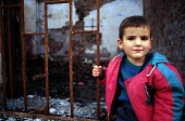 Kosovar Albanian child in the ruins of homes and a mosque destroyed by Serbs. Gjakova, Kosovo. 1999 - Howard Davies - &,1990s,1999,Albanian,Albanians,BALKAN,balkans,BAME,BAMEs,belief,BME,bmes,CHILD,CHILDHOOD,children,conflict,conflicts,conviction,diversity,ethnic,Ethnic Cleansing,ethnicity,europe,faith,GOD,housing,IS