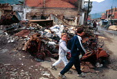 Children passing Kosovar Albanian houses destroyed by Serbs in ethnic cleansing. Peje, Kosovo. 1999 - Howard Davies - 01-05-1999
