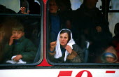 Kosovar Albanian refugees on a transit bus taking them away from the border. Blace refugee camp, Macedonia - Kosovo border. 1999 - Howard Davies - 1990s,1999,Albanian,Albanians,balkan,balkans,BAME,BAMEs,BME,bmes,border control,border controls,borders,bus,bus service,BUSES,camp,camps,CHILD,CHILDHOOD,children,conflict,conflicts,Diaspora,displaced,