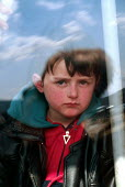 Kosovar Albanian refugee on a transit bus taking him away from the border. Blace refugee camp, Macedonia - Kosovo border. 1999 - Howard Davies - 1990s,1999,Albanian,Albanians,alone,balkan,balkans,border control,border controls,borders,bus,bus service,BUSES,camp,camps,CHILD,CHILDHOOD,children,conflict,conflicts,Diaspora,displaced,eu,europe,euro