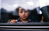 Kosovar Albanian refugee child on a transit bus taking them to a UNHCR / IOM evacuation flight to the UK. Stenkovic refugee camp, Macedonia. 1999 - Howard Davies - 01-05-1999