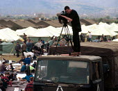 TV journalist, atop a NATO truck, reports on exodus of Kosovar Albanian refugees, Stenkovic refugee camp, Macedonia. 1999 - Howard Davies - 01-05-1999