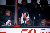 Kosovar Albanian refugees on a transit bus taking them away from the border. Blace refugee camp, Macedonia - Kosovo border. 1999 - Howard Davies - 1990s,1999,Albanian,Albanians,balkan,balkans,border control,border controls,borders,bus,bus service,BUSES,camp,camps,child,CHILDHOOD,children,conflict,Diaspora,displaced,eu,europe,european,europeans,F