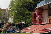 Street theatre performers Spiral Flight perform Caravan of Desires from the side of a caravan in the Streets of Brighton part of the Brighton Festival. Brighton, UK 2007 - Howard Davies - 2000s,2007,ace art arts,art,artist,ARTISTS,caravans,FEMALE,festival,FESTIVALS,Flight,FLIGHTS,flying,PEOPLE,person,persons,scene,scenes,Spiral,Street,Streets,theatre,THEATRES,woman,women