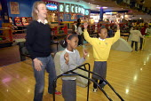 Refugee children, who came to the UK as refugees from Ethiopia under the Gateway Protection Programme, going bowling in Brighton with support workers. The majority of the refugees are Oromo and had be... - Howard Davies - 2000s,2007,aid agency,assistance,BAME,BAMEs,Black,BME,bmes,bowling,boy,boys,camp,camps,child,CHILDHOOD,children,Diaspora,displaced,diversity,Ethiopia,ethnic,ethnicity,female,females,foreign,foreigner,