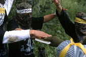 Palestinian militants swearing allegiance on a copy of the Koran during training for military action against Israeli forces Gaza. 2003 - Howard Davies - 01-07-2003
