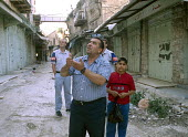 Two members of the TIPH international observer force watching a curfew confrontation between Palestinians and Israeli soldiers, Hebron West Bank 2003 - Howard Davies - 01-07-2003