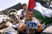 A Palestinian man shows a picture of his familys vintage Mercedes which was destroyed by Israeli forces, Gaza 2003 - Howard Davies - 2000s,2003,and,arab,arabs,bank,BANKS,CHILD,CHILDHOOD,children,conflict,conflicts,gaza,israel,Israeli,juvenile,juveniles,kid,kids,male,man,men,Mercedes,middle east,palestine,palestinian,palestinians,pe