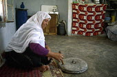 Palestinian woman grinding flour in her house, which is very close to the proposed security wall being constructed by Israel so faces eviction and demolition. Hebron District, West Bank 2003 - Howard Davies - 2000s,2003,and,arab,arabs,bank,BANKS,conflict,conflicts,EBF,Economic,Economy,employee,employees,Employment,FEMALE,flour,food,FOODS,gaza,Hebron,house,houses,housing,israel,job,jobs,LAB,LBR,Middle East,