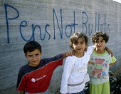 Palestinian children with graffiti whose school is twenty metres from the Israeli security fence, West Bank 2003 - Howard Davies - 2000s,2003,and,arab,arabs,bank,BANKS,child,CHILDHOOD,children,conflict,conflicts,edu,edu education,educate,educating,education,educational,fence,gaza,graffiti,Gun,guns,israel,Israeli,juvenile,juvenile