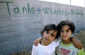 Palestinian children with graffiti whose school is twenty metres from the Israeli security fence, West Bank 2003 - Howard Davies - ,2000s,2003,and,arab,arabs,bank,BANKS,child,CHILDHOOD,children,conflict,conflicts,edu,edu education,educate,educating,education,educational,fence,gaza,graffiti,Gun,guns,israel,Israeli,juvenile,juvenil