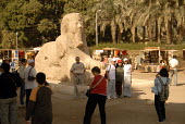 Tourists being photographed by an Alabaster Sphinx in the ruins of Memphis, once the ancient capital of the Old Kingdom of Egypt. - Howard Davies - 2000s,2006,ace arts culture,african,Africans,Alabaster,arab,arabic,arabs,artwork,artworks,attraction,attractions,BUILDING,BUILDINGS,camera,cameras,capital,construction,constructions,egypt,egyptian,FEM