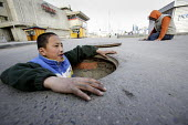 Street children lifting the heavy steel lids on manholes that cover the pipes that carry city heating water, Ulan Bataar. Mongolia. Street children use these holes as homes during the freezing winter... - Jim Holmes - 23-04-2007