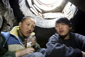 Street children hide in the darkness below a manholes that cover the pipes that carry city heating water. Street children use these holes as homes during the freezing winter months. Ulan Bataar. Mongo... - Jim Holmes - 23-04-2007