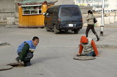 Street children lift the heavy steel lids on manholes that cover the pipes that carry city heating water. Street children use these holes as homes during the freezing winter months. Ulan Bataar. Mongo... - Jim Holmes - 23-04-2007