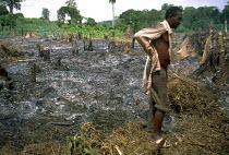 Farmer surveys land smoking having been cleared. Uganda. 1998 - Jim Holmes - 03-07-1998