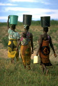 Women walk back to their village with water on thier heads. Uganda. 1998 The provision of clean drinking water prevents water borne disease. - Jim Holmes - 03-07-1998