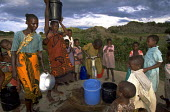 Families arriving to collect water at dusk. Uganda. 1997 The provision of clean drinking water prevents water borne disease. - Jim Holmes - 03-07-1997