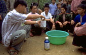 Women learn how to dip mosquito nets in a chemical which kills mosquitos to counter malaria. Vietnam. 1998 - Jim Holmes - 03-07-1998