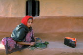 Girl preparing food for the family while listening to the radio. Nepal. 1998 - Jim Holmes - 03-07-1998