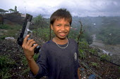 Boy with replica handgun he has found. Children work on vast mountains of rubbish on the civic dump on the edge of Manila where just months before a whole community had been buried. Philippines. - Jim Holmes - 03-07-2001