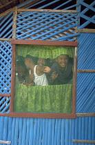 Children look through a screen window in a small village on Honda Bay, Palawan Island. Philippines. 2001 - Jim Holmes - 2000s,2001,asia,asian,asians,CHILD,CHILDHOOD,children,developing,Filipino,Filipinos,Honda,housing,juvenile,juveniles,kid,kids,life,people,Philipino,Philipinos,Philippine,philippines,rural,screen,villa