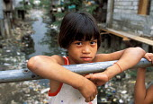 Girl playing on a bridge over an open sewer in an urban slum in Manila. Philippines. 2001 - Jim Holmes - .,2000s,2001,asia,asian,asians,boy,boys,bridge,child,CHILDHOOD,children,developing,disease,DISEASES,EBF,Economic,Economy,eni,environment,Environmental Issues,EQUALITY,excluded,exclusion,Filipino,Filip
