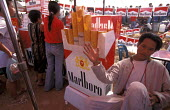 Large multinationals fight for a place in the market place demonstrate their branding skills with American cigarettes. Vientiane. Laos 2001 - Jim Holmes - 2000s,2001,American,americans,asia,asian,asians,CAPITALISM,capitalist,developing,globalisation,globalised,globalization,globalized,Health,lao,LAO418,laos,laotian,Laotians,life,market,Southeast asia,ur
