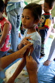 After the Tsunami a girl being vaccinated against measles at an IDP camp in a government building in the centre of Banda Aceh by volunteer doctors from other provinces of Indonesia. Aceh, Indonesia 20... - Jim Holmes - 03-04-2005