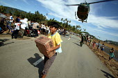 An Indonesian military helicopter lands on the road just seven kms from Banda Aceh town. A displaced boy carries a box of food away from the helicopter to residents of a village near Banda Aceh who ha... - Jim Holmes - 03-04-2005