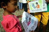 Children displaced by the Tsunami work with colouring sheets and pens featuring hygiene messages while bed nets are being distributed by Oxfam. Aceh, Indonesia 2005 - Jim Holmes - 03-04-2005