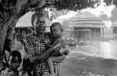 An Acholi woman with her child shlter from the rain in an IDP camp for Acholi displaced by the violent conflict waged between the Ugandan Government army - UPDF - and the Lords Resistance Army in nort... - Thomas Morley - 12-02-2005