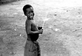 An Acholi child with a bow and arrow which is used to hunt bush rats in an IDP camp for Acholi displaced by the violent conflict waged between the Ugandan Government army - UPDF - and the Lords Resist... - Thomas Morley - 18-02-2005