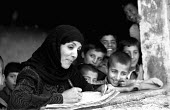 A woman teacher with children at an Afghan school reopened for girls and boys after the defeat of the Taliban. The school had been closed as it stood on the front line between the Taliban and Norhern... - Thomas Morley - 01-03-2002